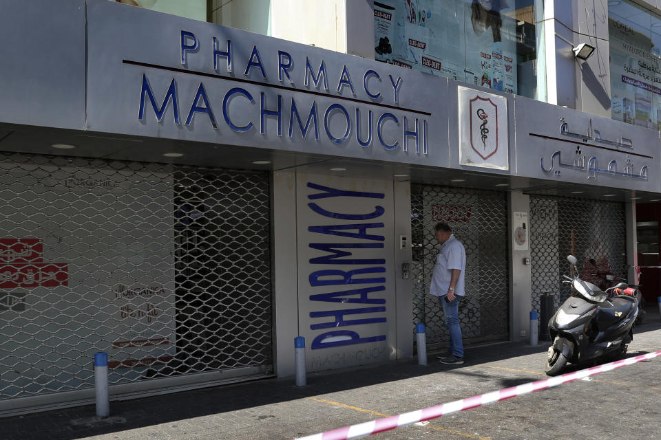 A man waits in front of a closed pharmacy in Beirut, Lebanon, Friday, June 11, 2021. Pharmacies across Lebanon began a two-day strike Friday, protesting severe shortages in medicinal supplies that is increasingly putting them in confrontation with customers and patients searching for medicines. The shortages are affecting everything from medicines for chronic illnesses to pain relievers to infant milk. (AP Photo/Bilal Hussein)