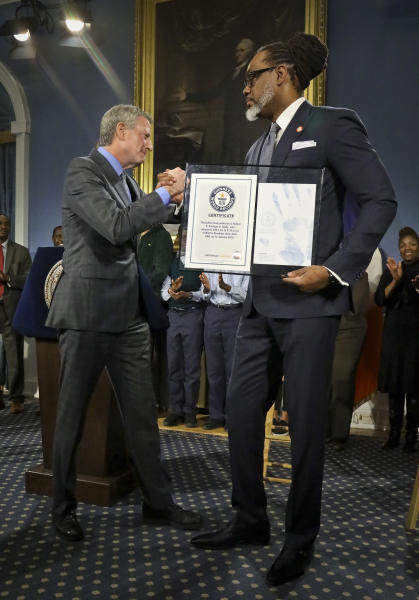 New York Mayor Bill de Blasio, left, awards N.Y. City Councilman Robert Cornegy, Jr. the Guinness World Record's tallest male politician, Wednesday March 27, 2019, at City Hall in New York. (AP Photo/Bebeto Matthews)