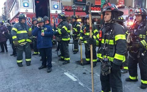 Fire brigade crew wait at the scene after an explosion occured at the Port Authority Bus Terminal in New York - Credit: Getty