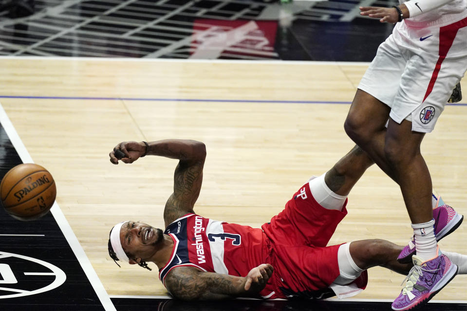 Washington Wizards guard Bradley Beal falls and loses the ball while under pressure from Los Angeles Clippers forward Marcus Morris Sr. during the second half of an NBA basketball game Tuesday, Feb. 23, 2021, in Los Angeles. The Clippers won 135-116. (AP Photo/Mark J. Terrill)