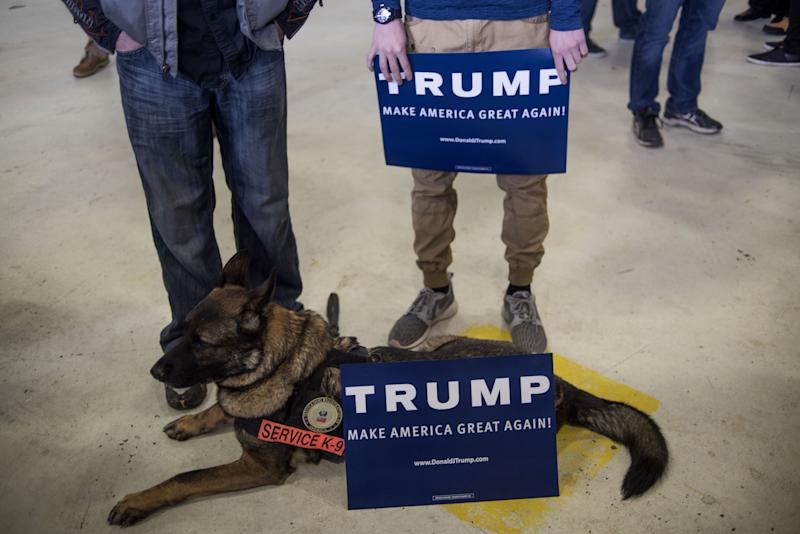 Attendees hold signs while standing by a service dog during a campaign rally for Donald Trump at the Port Columbus International Airport in Columbus, Ohio, on March 1, 2016.