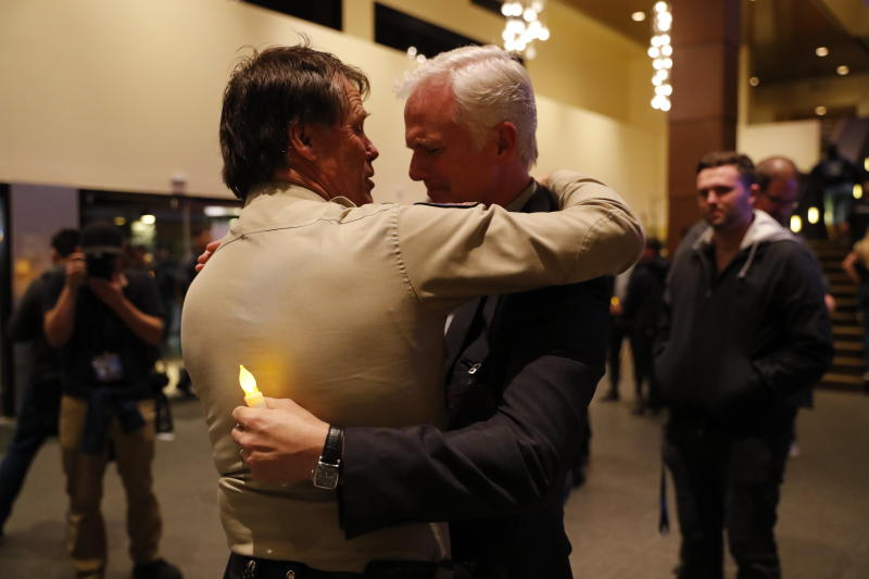 Thousand Oaks Police Chief Tim Hagel, left, hugs Officer Chris Dunn at the vigil. (Mike Blake / Reuters)