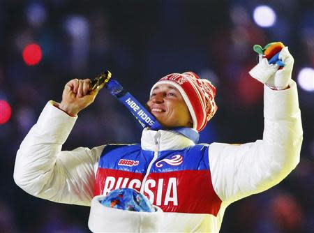 Russian gold medalist Alexander Legkov celebrates as he recieves his medal for the men's cross-country 50-kilometer mass start race during the closing ceremony for the Sochi 2014 Winter Olympics, February 23, 2014. REUTERS/Lucy Nicholson