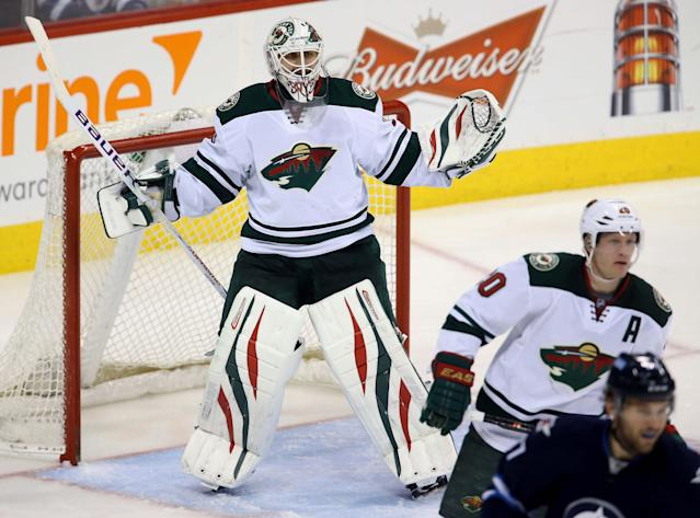 Minnesota Wild's Ilya Bryzgalov (30) taunts the crowd while they chant his name as play continues during third period NHL hockey action against the Winnipeg Jets in Winnipeg, Manitoba, on Monday, April 7, 2014. (AP Photo/The Canadian Press, Trevor Hagan)