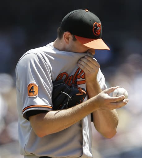 Baltimore Orioles starting pitcher Jason Hammel wipes his face with his jersey during the first inning of a baseball game against the New York Yankees on Sunday, July 7, 2013, in New York. (AP Photo/Kathy Willens)