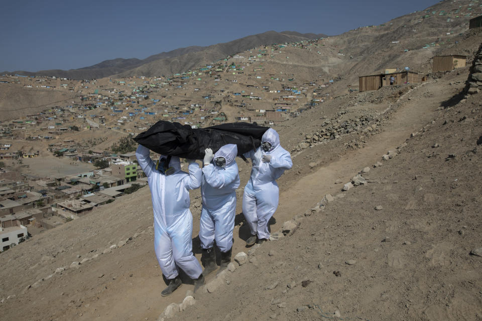 """Piedrangel funeral home workers Luis Zerpa, Luis Brito, center, and Jhoan Faneite, right, from Venezuela, carry the body of Marcos Espinoza, 51, who died from coronavirus in his precarious house in a poor neighborhood in Pachacamac on the outskirts of Lima, Peru, on May 8, 2020. Photographer Rodrigo Abd said the image encapsulates the injustices that the pandemic exposed: the plight of Venezuelan migrant funeral workers doing a job to survive despite the risks; the high mortality rate among Peru's poorest and the harshness of the desert landscape around Lima, where over 10 million people live without water or basic services. """"I will never forget this image for all that it represents,"""" Abd said. (AP Photo/Rodrigo Abd)"""