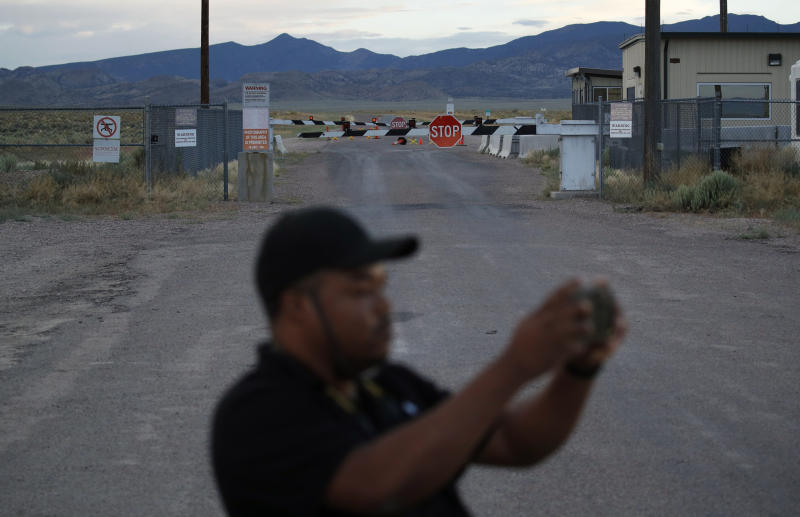 FILE - In this July 22, 2019, file photo, Terris Williams visits an entrance to the Nevada Test and Training Range near Area 51 outside of Rachel, Nev. Two men from the Netherlands who said they wanted to post internet video of the once-secret Area 51 military base in Nevada were arrested on suspicion of trespassing onto a secure U.S. government reservation, sheriff's officials said Thursday, Sept. 12, 2019. (AP Photo/John Locher, File)