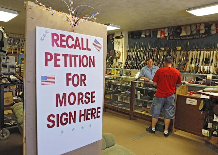 In this photo taken May 24, 2013, a large sign posted at the entrance of Paradise Firearms in Colorado Springs, Colo., invites customers to sign a recall petition against Colorado Democratic State Senate President John Morse. In gun-friendly Colorado, gun-rights activists with support of the National Rifle Association are seeking Morse's ouster for his support of new laws that restrict ammunition magazines and expand background checks to private gun sales. (AP Photo/Ed Andrieski)