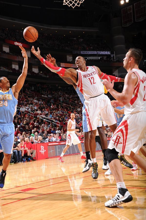 HOUSTON, TX - NOVEMBER 16: Dwight Howard #12 of the Houston Rockets rebounds the ball against the Denver Nuggets on November 16, 2013 at the Toyota Center in Houston, Texas. (Photo by Bill Baptist/NBAE via Getty Images)