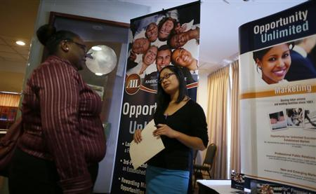Charmaine Lam from the company American Income talks to a job seeker at a job fair in Los Angeles