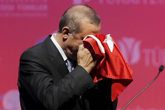 <p>Turkey's President Tayyip Erdogan kisses a handmade Turkish flag, given to him as a gift from Ugandan university student Cemil (not pictured), during a graduation ceremony in Ankara, Turkey, June 11, 2015. (Umit Bektas/Reuters) </p>
