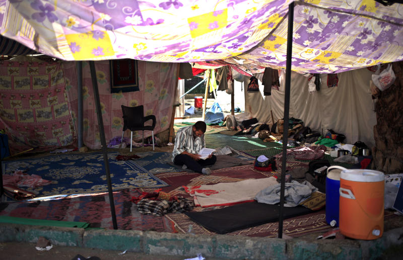 A supporter of Egypt's ousted President Mohammed Morsi reads Quran in a tent at a camp near Cairo University in Giza, Egypt, Thursday, July 25, 2013. The Muslim Brotherhood's leader on Thursday made an unusually harsh attack on Egypt's military chief, saying his ouster of President Mohammed Morsi was a worse crime than even destroying the Kaaba, Islam's holiest shrine. (AP Photo/Khalil Hamra)