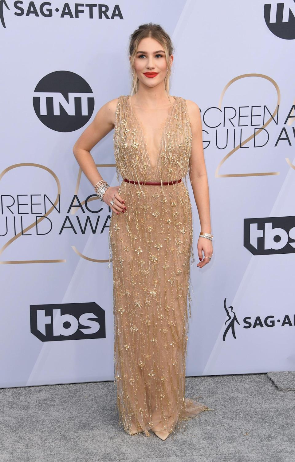 <p>Wearing a sheer gold gown by Marchesa.</p>