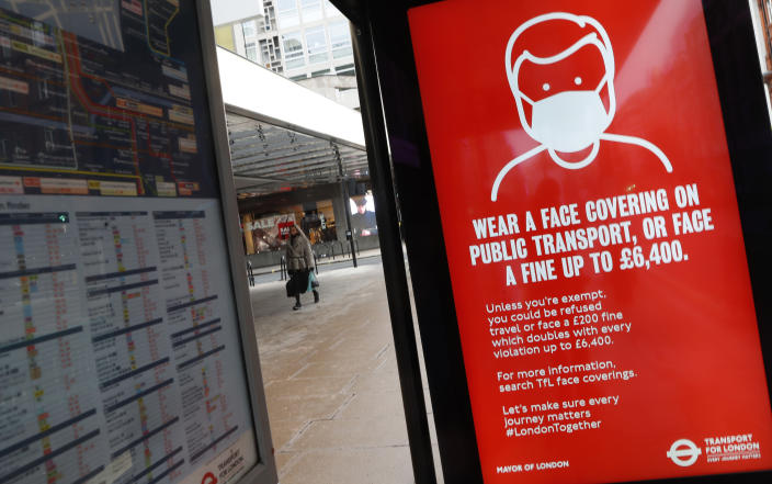 A digital display on a bus stop tells passengers that it is mandatory to wear a mask to prevent the spread of COVID-19 on public transport in London, Tuesday, Jan. 26, 2021. The U.K. will soon become the fifth country in the world to record 100,000 COVID-19 deaths, after the United States, Brazil, India and Mexico — all of which have much larger populations than Britain's 67 million people. As of Monday, the U.K.'s official coronavirus death toll was 98,531. (AP Photo/Alastair Grant)