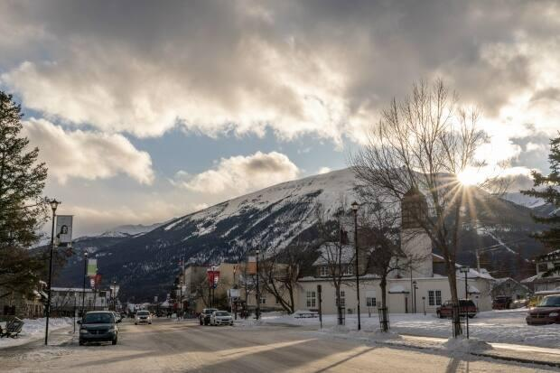 The sun peeks over a mountain in Jasper in this May 2020 file photo. The area is under a winter storm warning.  (Vincent Bonnay/Radio-Canada - image credit)