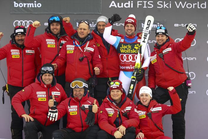 Switzerland's Beat Feuz, second from right in the back row, celebrates with the Swiss team after finishing second in an alpine ski, men's World Cup downhill, in Bormio, Italy, Friday, Dec. 27, 2019. (AP Photo/Alessandro Trovati)