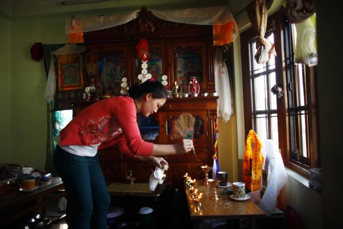 Phinjum Sherpa, 17, daughter of Ang Kaji Sherpa, killed in an avalanche on Mount Everest, lights a butter lamp in front of a portrait of her father in their rented apartment in Katmandu, Nepal, Wednesday, April 23, 2014. Dozens of Sherpa guides packed up their tents and left Mount Everest's base camp Wednesday, after the avalanche deaths of 16 of their colleagues exposed an undercurrent of resentment by Sherpas over their pay, treatment and benefits. (AP Photo/Niranjan Shrestha)