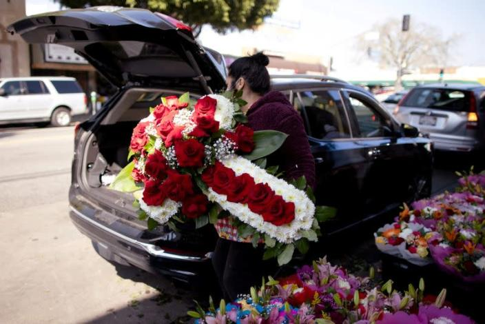 A woman lifts a funeral display into a car in the flower district in Los Angeles