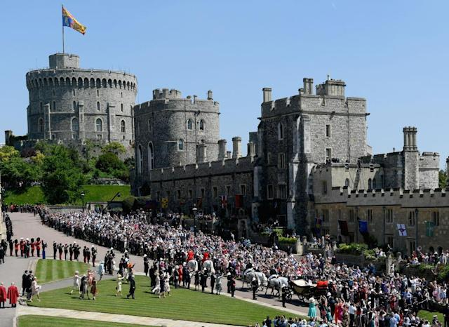 <p>Hundreds of thousands of wellwishers flocked to Windsor Castle to catch a glimpse of the royal couple during the procession. (Photo: Getty) </p>