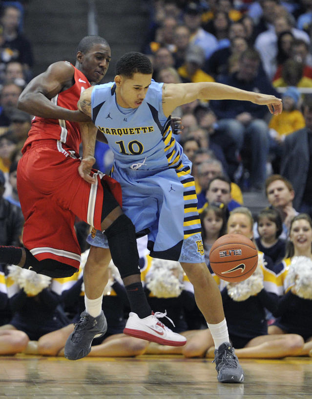 Ohio State's' Shannon Scott left, and Marquette's 's Juan Anderson (10) fight for the ball during the first half of an NCAA college basketball game, Saturday, Nov. 16, 2013, in Milwaukee. (AP Photo/Jim Prisching)