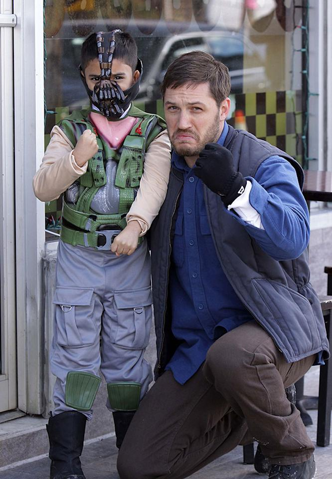 Tom Hardy pictured taking a photograph with a child dressed as 'Bane' while taking a break on the set of the 'Animal Rescue' movie in Flatlands Avenue in Brooklyn, NYC.