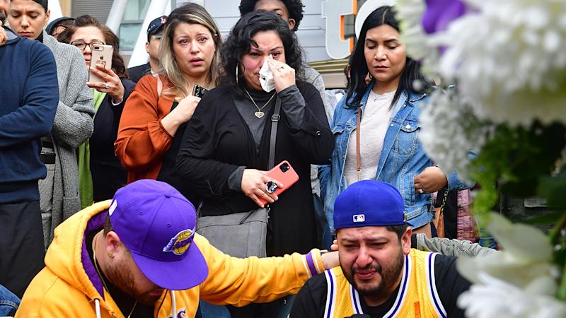 People gather around a makeshift memorial for Kobe Bryant, pictured here at Staples Centre.