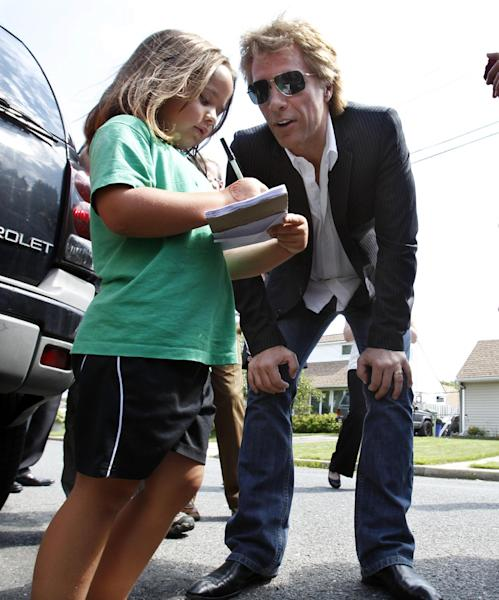 Singer Jon Bon Jovi asks five-year-old Brooklynn Melton if she is giving him her autograph Monday, July 8, 2013, as he walks in his hometown of Sayreville, N.J., with New Jersey Gov. Chris Christie. Bon Jovi is giving $1 million to help the band's home state recover from Superstorm Sandy. Bon Jovi has been a high-profile presence in his hometown since some neighborhoods were wiped out by Sandy last year. The singer says he wants to do what he can to help, including telling the world about the central New Jersey community's struggles. (AP Photo/Mel Evans, Pool)