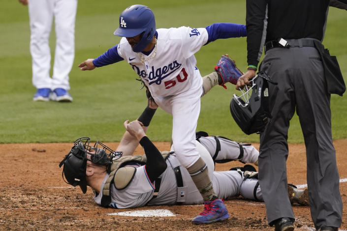 Miami Marlins catcher Chad Wallach, bottom, tags out Los Angeles Dodgers' Mookie Betts (50) at home during the fifth inning of a baseball game Sunday, May 16, 2021, in Los Angeles. Betts ran home after a single hit by Adam Duvall. (AP Photo/Ashley Landis)