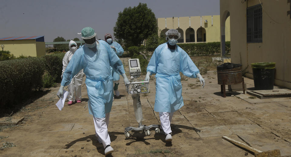 Medical works moving medical equipment while wearing PPE in Chad.