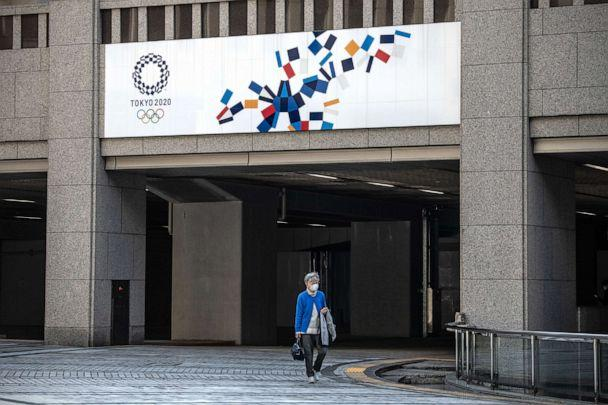 PHOTO: A woman walks beneath a Tokyo 2020 Olympics banner, March 19, 2020, in Tokyo, Japan. (Carl Court/Getty Images)