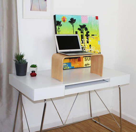 This modern bent wood laptop stand turns any desk into a standing desk.<span>Shop it here</span>.