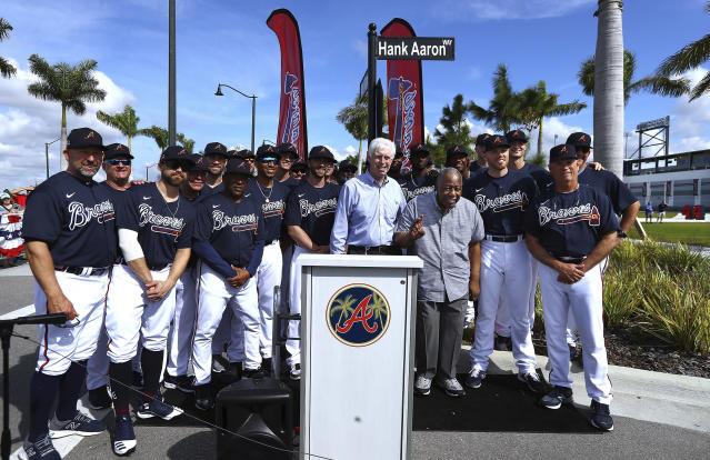 Atlanta Braves Chairman Terry McGuirk, center, and members of the Atlanta Braves baseball team honor baseball Hall of Famer Hank Aaron, third from right, front, with a street named after him outside CoolToday Park, the spring training baseball facility of the Braves, in North Port, Fla., Tuesday, Feb. 18, 2020 (Curtis Compton/Atlanta Journal-Constitution via AP)