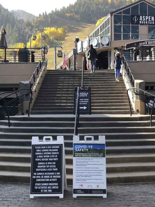 In this Oct. 3, 2020 photo, visitors climb the stairs past COVID-19 safety signs to the gondola at Aspen Mountain in Aspen, Colo. Aspen has become a popular destination during the coronavirus pandemic with its plethora of outdoor activities and precautions being taken by the town. (AP Photo/John Marshall)