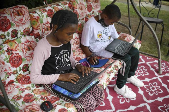 """FILE - In this Friday June 5, 2020, file photo, fourth-grader Sammiayah Thompson, left, and her brother, third-grader Nehemiah Thompson, work outside in their yard on laptops provided by their school system for distant learning in Hartford, Conn. The Senate's $1 trillion bipartisan infrastructure plan includes a $65 billion investment in broadband that the White House says will """"deliver reliable, affordable, high-speed internet to every household."""" It may not actually achieve that, but it's a major step. (AP Photo/Jessica Hill, File)"""