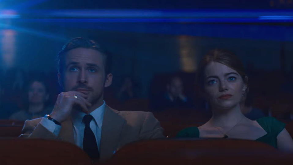 Ryan Gosling and Emma Stone bask in the glow of the cinema screen in 'La La Land'. (Credit: Lionsgate)