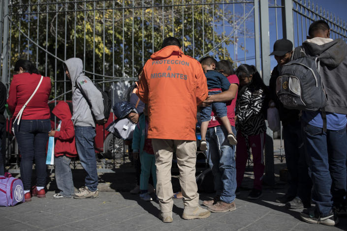 A representative from Grupos Beta collects the names and list numbers from asylum seekers after they arrived in a group of 30 from Casa Del Migrante in Juarez, Mexico, on Nov. 28, 2018. (Photo: Adria Malcolm for Yahoo News)