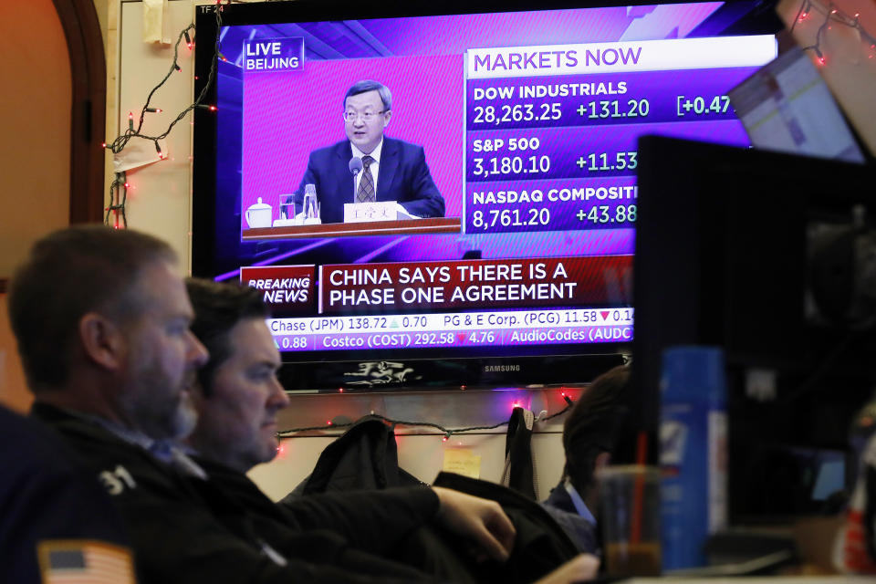 A television screen on the floor of the New York Stock Exchange, Friday, Dec. 13, 2019, shows a press annuncement in China. After months of waiting, markets had a muted reaction to news Friday that the US and China had reached an initial deal on trade. (AP Photo/Richard Drew)