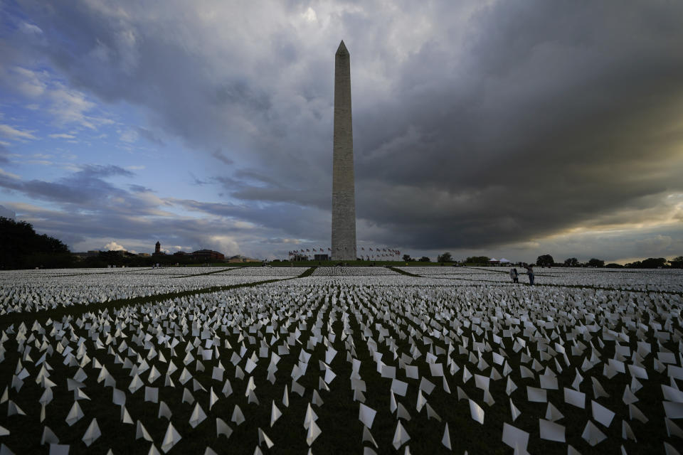"""With the Washington Monument in the background, people look at white flags that are part of artist Suzanne Brennan Firstenberg's temporary art installation, """"In America: Remember,"""" in remembrance of Americans who have died of COVID-19, on the National Mall in Washington, Friday, Sept. 17, 2021. The installation consists of more than 630,000 flags. (AP Photo/Brynn Anderson)"""