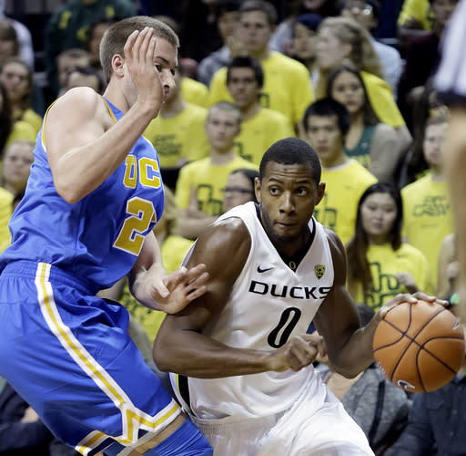 Oregon forward Mike Moser, right, drives on UCLA forward Travis Wear during the first half of an NCAA college basketball game in Eugene, Ore., Thursday, Jan. 30, 2014. (AP Photo)