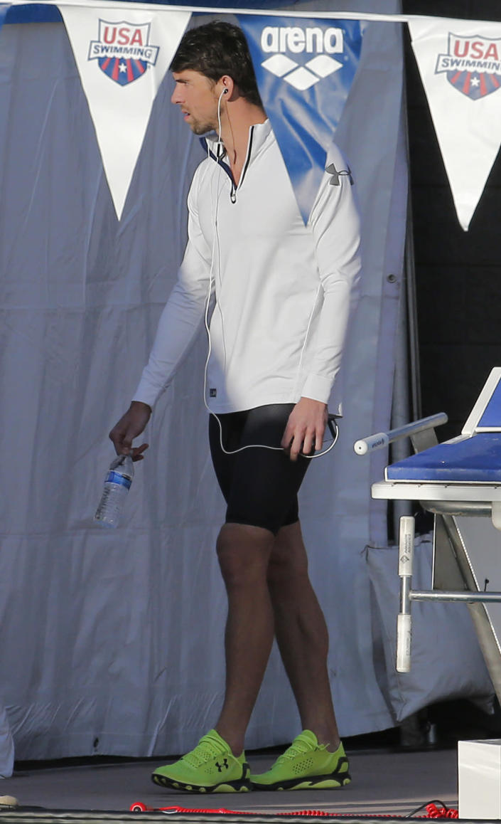 Michael Phelps arrives for the 100-meter butterfly final during the Arena Grand Prix, Thursday, April 24, 2014, in Mesa, Ariz. Phelps finished second in the final. (AP Photo/Matt York)