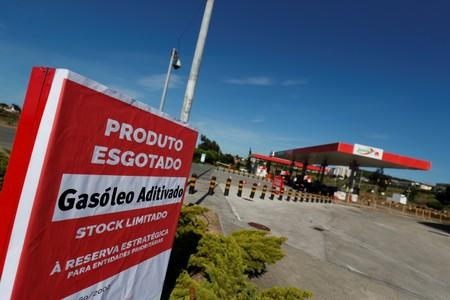 """A placard reading """"Diesel sold out"""" is seen at a gas station in Lisbon"""