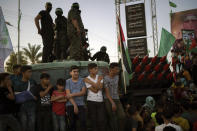 Palestinians gather as Hamas militants parade at a rally just over a week after a cease-fire was reached in an 11-day war between Hamas and Israel, Sunday, May 30, 2021, in Beit Lahia, northern Gaza Strip. (AP Photo/Felipe Dana)