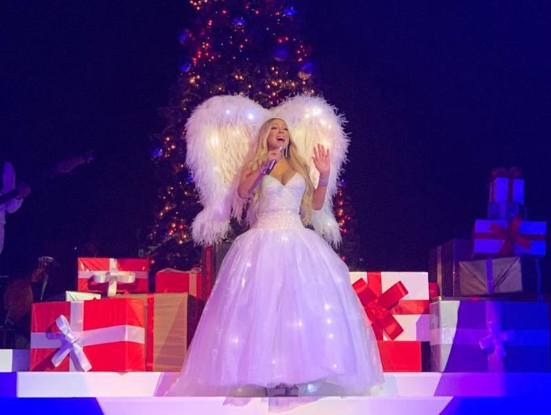 Just for good measure, here's Mariah once again, wearing actual feathered wings. (Feathers are a great choice for the holidays, in case you were wondering.) Oh, and of course the whole outfit lights up, just as a Christmas tree lights up.