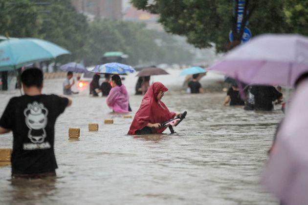 TOPSHOT - This photo taken on July 20, 2021 shows people wading through flood waters along a street following heavy rains in Zhengzhou in China's central Henan province. - - China OUT (Photo by STR / AFP) / China OUT (Photo by STR/AFP via Getty Images) (Photo: STR via AFP via Getty Images)