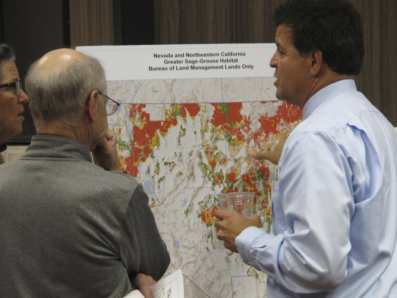 FILE - In this Nov. 7, 2017 file photo, Raul Morales, right, the U.S. Bureau of Land Management's deputy state director for Nevada, looks at a map of sage grouse habitat areas on BLM lands in Nevada and Northeastern California during a public meeting in Sparks, Nev. Federal land managers have withdrawn more than 500 square miles (1,295 sq. kilometers) of public land from a swath of eastern Nevada where oil and gas drilling leases were scheduled to be auctioned off on Tuesday, Nov. 12, 2019, after a judge blocked the Trump administration's attempt to ease protection of sage grouse habitat. (AP Photo/Scott Sonner, File)