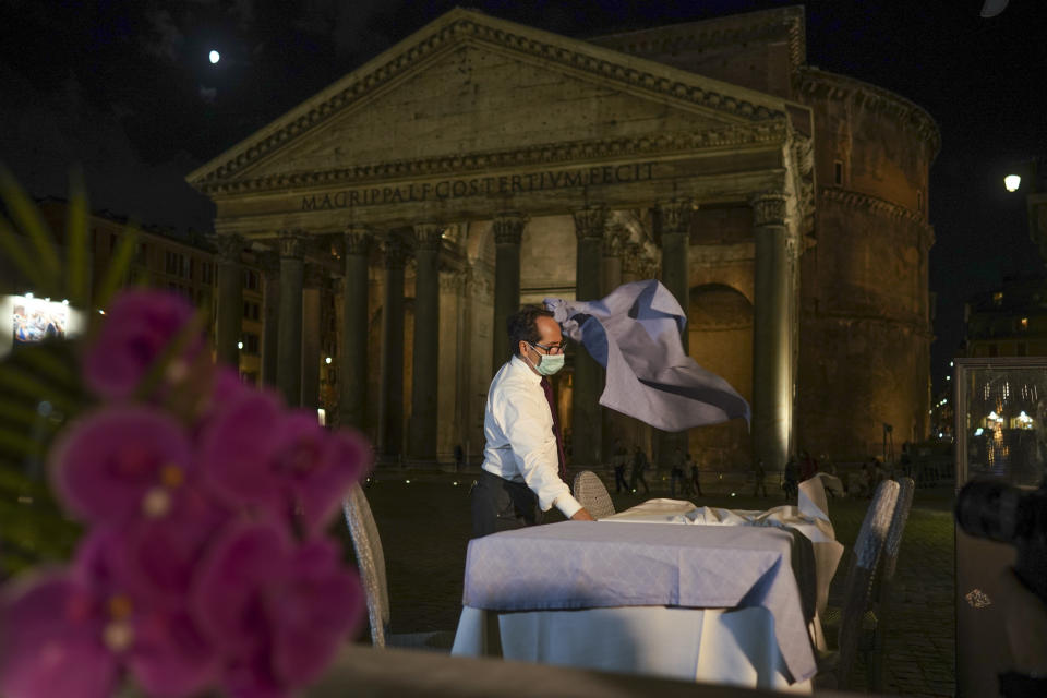 A waiter clears a table before closing a restaurant in front of the Pantheon, Rome, Monday, Oct. 26, 2020. For at least the next month, people outdoors except for small children must now wear masks in all of Italy, gyms, cinemas and movie theaters will be closed, ski slopes are off-limits to all but competitive skiers and cafes and restaurants must shut down in early evenings, under a decree signed on Sunday by Italian Premier Giuseppe Conte, who ruled against another severe lockdown despite a current surge in COVID-19 infections. (AP Photo/Andrew Medichini)
