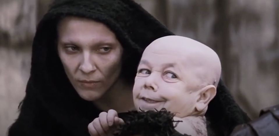A cloaked figure holds a toddler who is wearing a sinister grin
