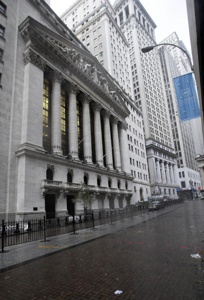 The streets surrounding the New York Stock Exchange, left, are deserted as financial markets remain closed for the second day,Tuesday, Oct. 30, 2012. Sandy, the storm that made landfall Monday, caused multiple fatalities, halted mass transit and cut power to more than 6 million homes and businesses. (AP Photo/Richard Drew)
