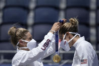 April Ross, left, of the United States, places the gold medal around the neck of teammate Alix Klineman, after winning a women's beach volleyball Gold Medal match against Australia at the 2020 Summer Olympics, Friday, Aug. 6, 2021, in Tokyo, Japan. (AP Photo/Felipe Dana)