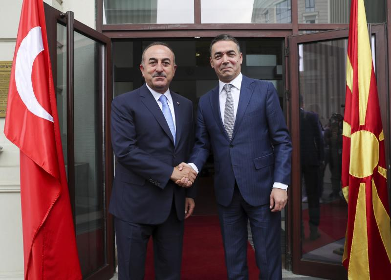 """Turkey's Foreign Minister Mevlut Cavusoglu, left, shakes hands with North Macedonia's Foreign Minister Nikola Dimitrov, right, prior to their meeting, in Skopje, North Macedonia, Tuesday, July 16, 2019. Cavusoglu on Tuesday downplayed as """"worthless"""" an initial set of sanctions approved by the European Union against Ankara and vowed to send a new vessel to the eastern Mediterranean to reinforce its efforts to drill for hydrocarbons off the island of Cyprus. EU foreign ministers on Monday approved sanctions against Turkey over its drilling for gas in waters where EU member Cyprus has exclusive economic rights. (Cem Ozdel/Turkish Foreign Ministry via AP, Pool)"""